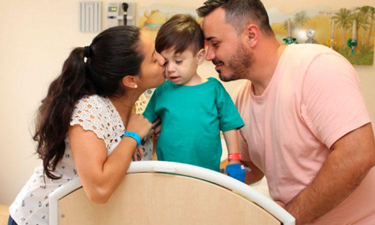 Foto horizontal de um garotinho em uma cama de hospital sendo beijado, de cada lado do rosto, por seus pais.