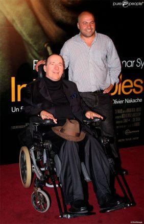 Foto vertical de dois homens lado a lado. Sentado em uma cadeira de rodas, à esquerda, Philippe di Borgio, em uma roupa predominantemente preta. À direita, em pé, o argelino Abdel Sellou, com uma blusa social cinza e calça preta. Atrás deles, o cartaz do filme Os Intocáveis