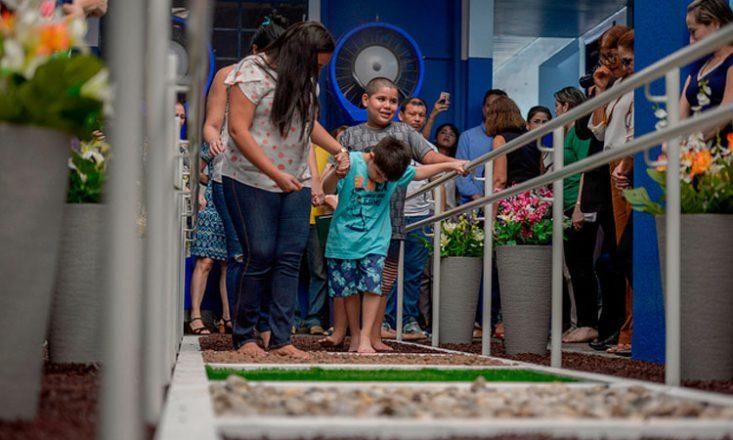 Menino com autismo caminha por um jardim sensorial, apoiado por uma mulher que segura sua mão. Várias pessoas o observam ao seu redor.