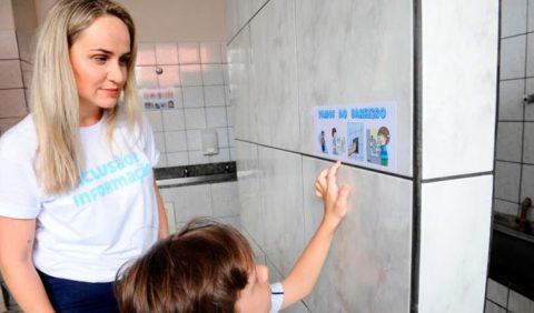 Foto de uma mãe loira, vestindo uma camiseta branca com os dizeres INCLUSÃO E INFORMAÇÃO, em azul, junto com seu filho. O garoto aponta para um adesivo na parede, informando que ali é a entrada do banheiro da escola