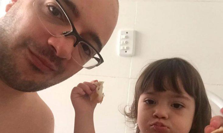 Pai e filha comem pão na cozinha de casa.
