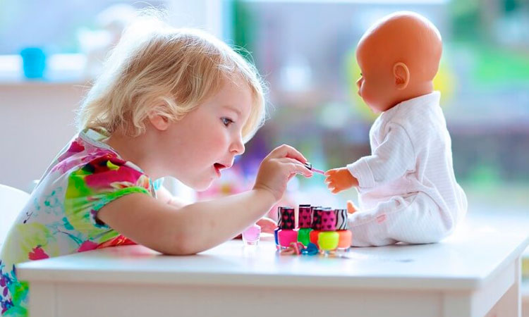 Garotinha loira brinca com uma boneca em cima da mesa, pintando suas unhas. Ao lado, vários frascos de esmalte de variadas cores.
