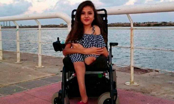 Jovem moça em uma cadeira de rodas, com a perna esquerda amputada. Ao fundo, o mar.