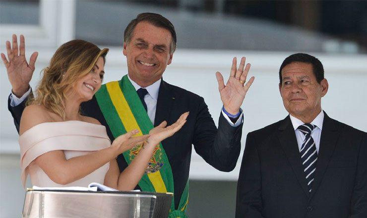 Três pessoas de frente para a foto. À esquerda, uma mulher de vestido claro sorri e aponta as mãos para o homem ao centro, de paletó e a faixa presidencial ao peito e um segundo homem, à direita, também de paletó.