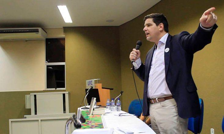 Homem de blazer azul escuro fala ao microfone em um auditório e aponta para sua esquerda com a mão.