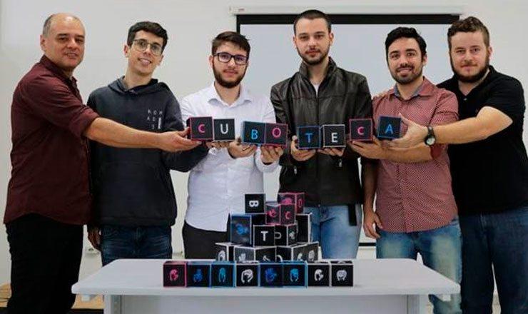 Seis homens lado a lado, cada um segurando um pequeno cubo com uma letra colorida neles, formando a palavra CUBOTECA. A sua frente, uma mesa, com mais uma dezena de outros cubos.