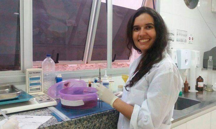Jovem médica vestindo bata branca, sorrindo, em um laboratório