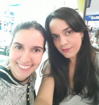 Duas jovens posam juntas no que parece ser um shopping, sorrindo para a câmera