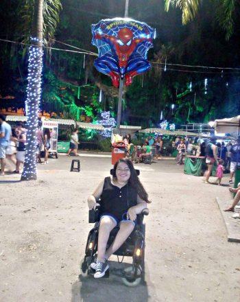 Foto vertical de uma jovem sorrindo em uma cadeira de rodas, no Campo de São Bento/Niterói, em 2018. Ao fundo, várias pessoas passeando, visitando barraquinhas e conversando. No alto, um balão com a imagem do Homem Aranha.