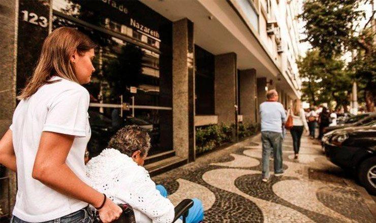 Foto horizontal de uma calçada do Rio de Janeiro, com uma jovem empurrando a cadeira de rodas de um idoso, em primeiro plano, e algumas pessoas caminhando mais a frente.