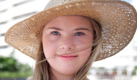 Foto do rosto de uma adolescente loira com Síndrome de Down, usando um chapéu de palha, com os cabelos sobre o rosto.
