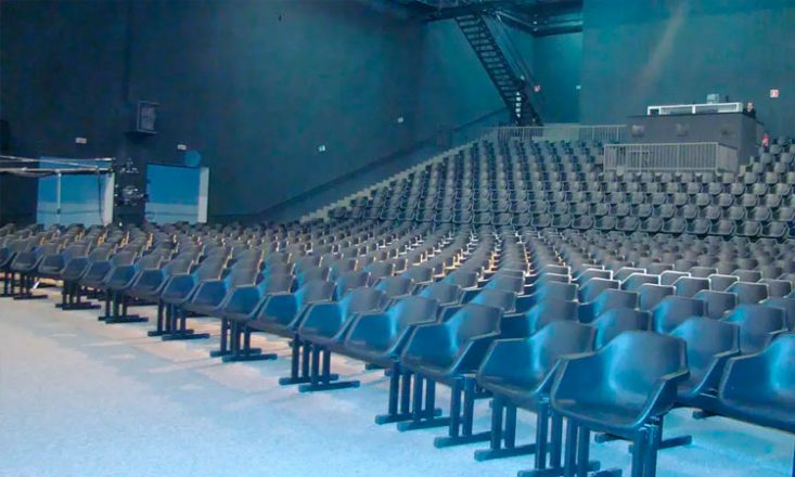 Imagem mostra um auditório completamente vazio, na cor predominante de azul