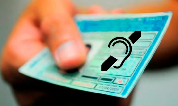 Uma mão segura uma carteira de motorista. Em cima dela, o símbolo internacional da pessoa surda, uma orelha preta com um traço em diagonal sobre ela.
