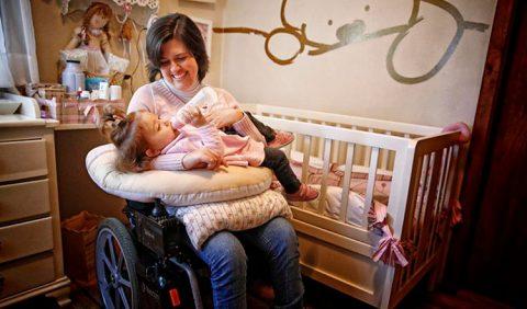 Em um quarto de bebê, mulher em uma cadeira de rodas sorri enquanto dá a mamadeira para sua filha deitada em duas almofadas no colo dela. Ao lado, um berço e, atrás, a cômoda com bonecas e material de higiene.