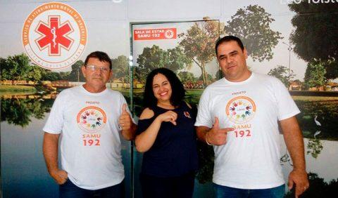 Três pessoas, dois homens e uma mulher no meio, lado a lado, sorriem. Vestem camisas do Samu e têm a logomarca do Sistema no alto do lado esquerdo.