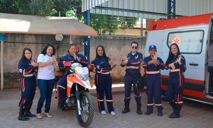 Sete profissionais do Samu fazem gestos de Libras para a câmera. Uma delas está sentada em uma moto e há uma ambulância do lado direito da imagem. Todos vestem o uniforme azul do Samu, com exceção de uma, que veste uma camiseta branca.