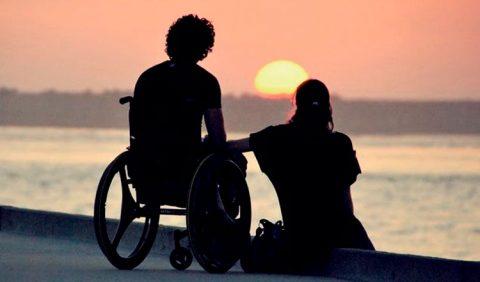 Casal observa o pôr do sol no calçadão de uma praia, ele em uma cadeira de rodas e ela sentada ao seu lado, de mãos dadas. Eles estão em primeiro plano, de costas, com a imagem escurecida. Ao fundo, o mal e o sol por trás das montanhas.