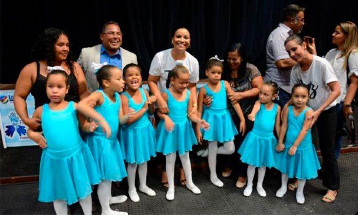 Sete meninas autistas vestindo collants azuis durante aula de balé, acompanhadas de mães e um professor.