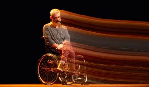 Homem em uma cadeira de rodas, com braços e pernas cruzadas, em um palco de teatro. Do lado direito, raios de luz saem dele, um efeito visual de imagem dando a sensação de movimento. Ao fundo, uma tela preta.
