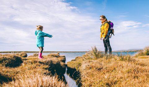 Mãe (à dir) e sua filha, em viagem, se olham de frente uma para a outra. Ao fundo, o céu azul, nuvens e o oceano.