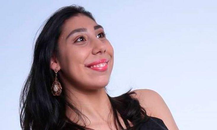 Foto do rosto de uma jovem de 20 anos, sorrindo e olhando para seu lado esquerdo. Ao fundo, uma tela azul claro.