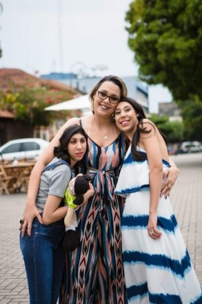 Foto vertical em uma rua de três mulheres. A mais velha, ao centro, abraça as duas filhas, uma de cada lado.