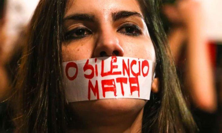 Rosto de uma mulher com um adesivo na boca escrito, em letras vermelhas: O SILÊNCIO MATA.