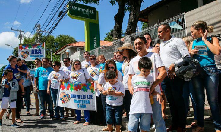Grupo de vários pais, mães e crianças se manifestando em frente à sede da Unimed/CE, com um cartaz com o símbolo do Autismo e os dizeres: UNIMED MANTENHA O ABA
