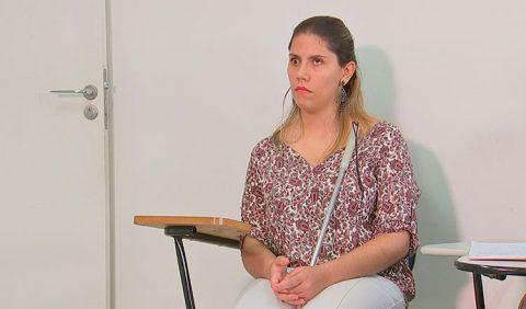 Mulher cega sentada em uma cadeira escolar, com sua bengala no colo.