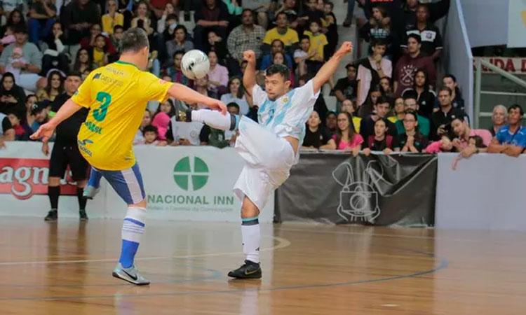Dois rapazes com Síndrome de Down disputam uma jogada de futsal. À esquerda, o jogador veste a camisa amarela da seleção brasileira e, à direita, o jogador veste a camisa listrada em branco e azul da Argentina. Ao fundo, o juiz observa o lance e, atrás dele, arquibancada cheia de torcedores.
