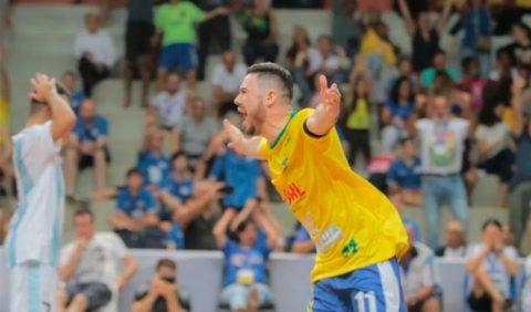 Jogador da seleção brasileira de futsal Down comemora, de braços abertos e largo sorriso no rosto. À esquerda, em segundo plano, jogador da seleção argentina coloca as mãos na cabeça, em sinal de desespero.