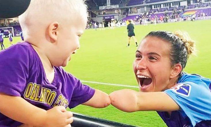 Jogadora de futebol brinca com um bebê na arquibancada, ambos nasceram sem o antebraço e a mão.