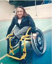 Foto de Leandra sentada em uma cadeira de rodas. Ela está com calça cinza, blusa branca e casaco preto.
