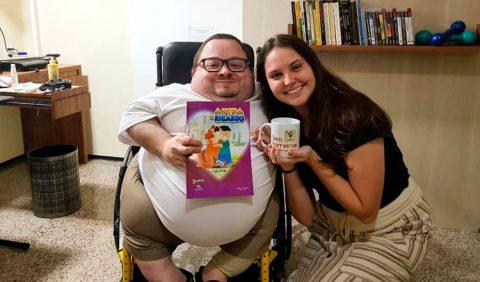 Victor Vasconcelos, na cadeira de rodas, segurando o livro A Vida de Ricardo, ao lado de Lígia Grillo, com a caneca do blog Sem Barreiras nas mãos. Ao fundo, uma estudante com livros e DVDs e uma mesa do lado esquerdo.