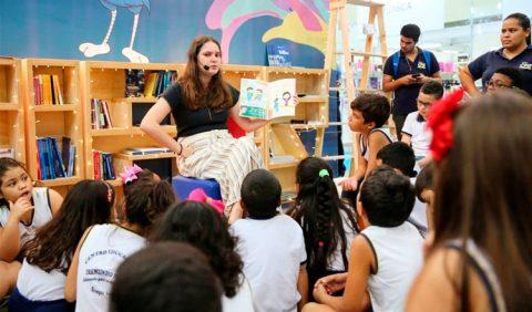 Lígia sentada ao centro, com um microfone e um livro aberto na mão, contando histórias para dezenas de crianças sentadas no chão ao redor dela.