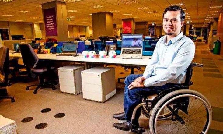 Homem em uma cadeira de rodas, de lado, sorrindo, no canto direito da imagem. À esquerda, uma mesa com dois computadores e vários enfeites.