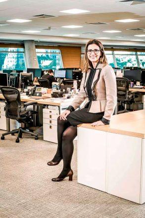 Foto de uma mulher sentada em uma bancada, sorrindo, de óculos, trajada com um casaco executivo bege, saia e meias pretas