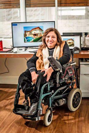 Mulher de meia idade, elegantemente trajada, em uma cadeira de rodas motorizada no que parece ser um escritório de arquitetura.