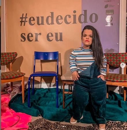 Jovem com nanismo de pé em meio a três cadeiras e roupas espalhadas pelo chão. Atrás dela, na parede, os dizeres #eudecido ser eu