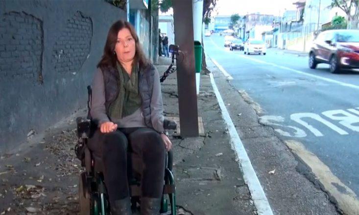 Mulher em uma cadeira de rodas parada em uma calçada cheia de buracos e imperfeições. Do lado direito, a rua com vários carros passando.