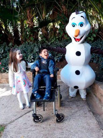 Allice e Vitor, na sua cadeira de rodas, riem ao lado do boneco Olaf, personagem do desenho Frozen, da Disney,