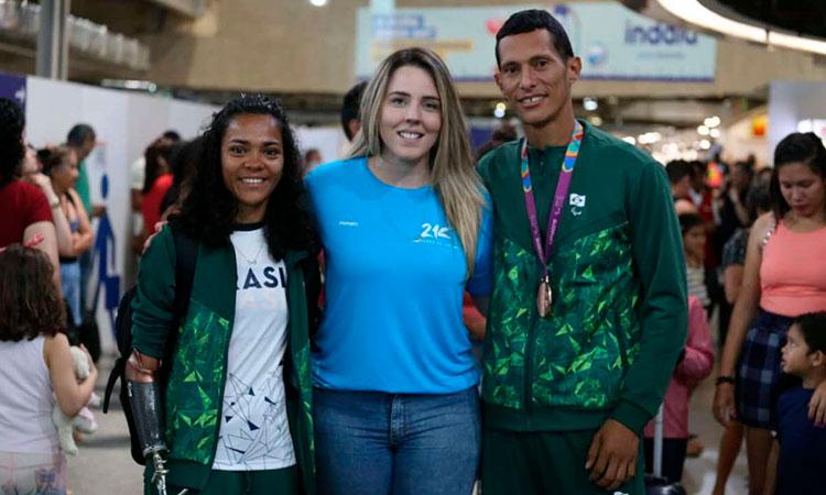 Foto de dois atletas dos jogos parapan de Lima (Peru), à esquerda e à direita da imagem, sendo recepcionados no aeroporto por uma jovem loira de blusa azul e calça jeans, ao centro. Ao fundo, várias outras pessoas caminhando aleatoriamente.