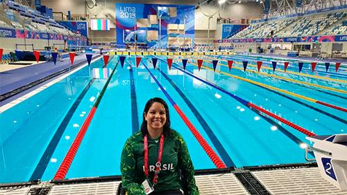 Foto de uma nadadora brasileira sentada à margem de uma piscina, com o agasalho verde do Brasil e uma medalha no peito. Atrás dela, a piscina, arquibancadas e várias bandeirinhas coloridas.
