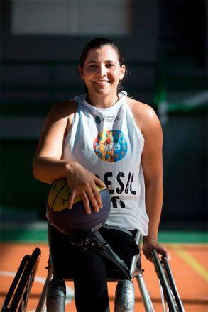 Foto vertical de uma mulher, sorrindo, sentada em uma cadeira de rodas, segurando uma bola de basquete.