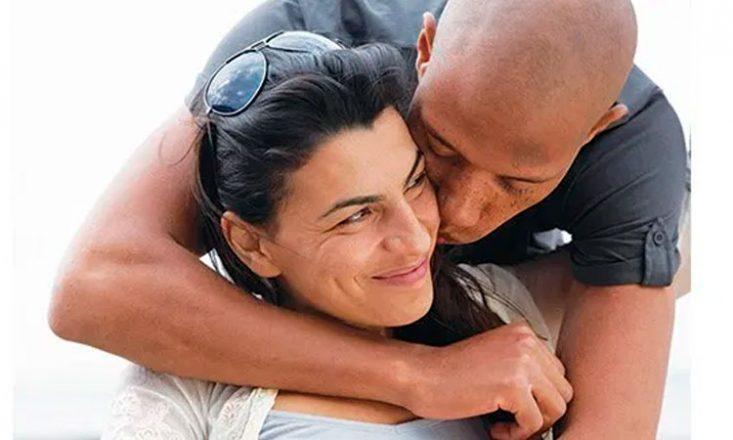 Casal se abraça carinhosamente. A mulher na frente, sentada e sorrindo, e o homem, mulato, a enlaçando por trás na altura do pescoço e beijando seu rosto do lado esquerdo.