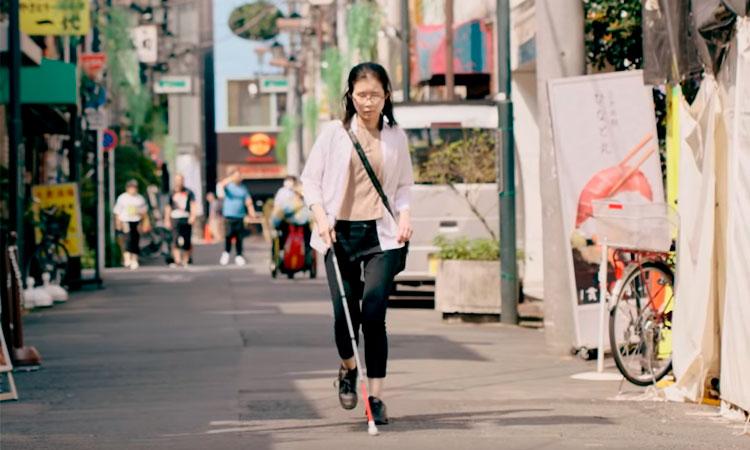 Mulher cega caminha por uma rua, usando sua bengala.
