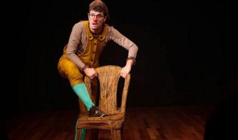 Homem vestido de palhaço, sozinho na imagem, com uma cadeira a sua frente. Ele segura seu encosto e seu pé direito está sobre o acento. Por trás, uma tela negra.