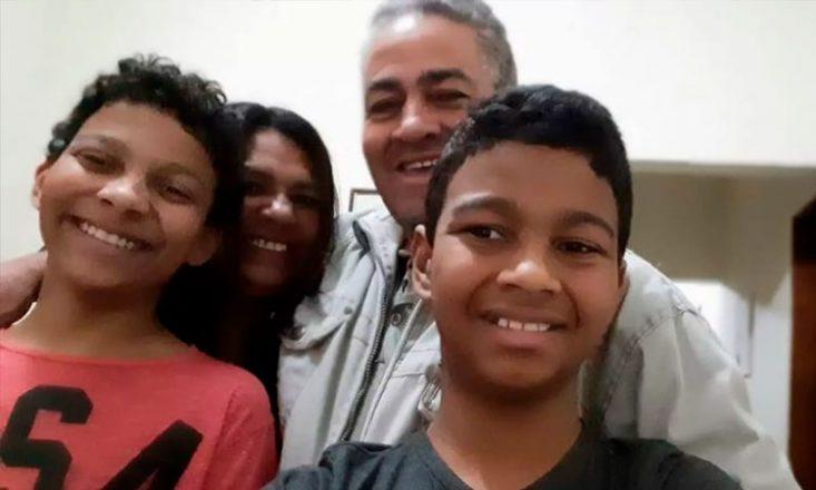 Quatro pessoas de uma família, dois garotos, em primeiro plano, o pai e a mãe ao fundo.