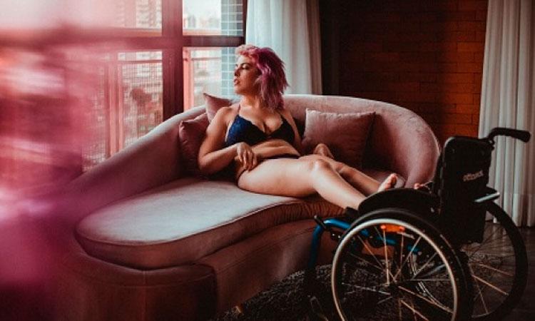 Foto de uma mulher somente de lingerie, deitada em um sofá, com os pés sobre uma cadeira de rodas, olhando para seu lado direito. A imagem tem uma coloração de rosa, predominante, assim com os cabelos dela têm a mesma cor.