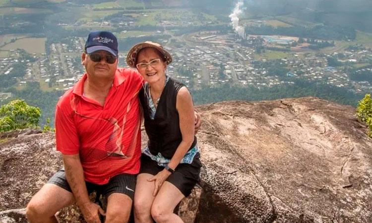 Casal sentado em uma pedra, no alto de uma montanha. Ao fundo, a imagem de uma cidade, bem pequenininha.